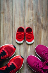 Three red sport running shoes or sneakers of mother and father and child on wooden background,use for father's day or mother's day or family's day with sport active lifestyle concept with copy space
