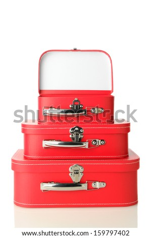 Three red suitcases stacked on a white background with slight reflection. Top bag is open. Vertical format.