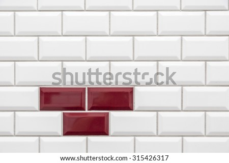 Three red tiles in many white tiles