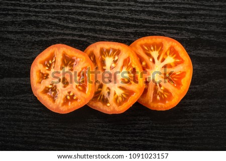 Three red tomato slices top view isolated on black wood background cut in circles #1091023157