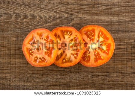Three red tomato slices top view isolated on brown wood background cut in circles #1091023325