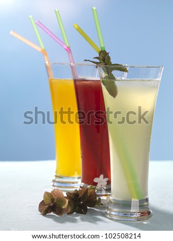 three refreshments,strawberry, lemon and orange homemade juices on a white surface