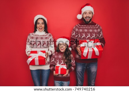 Three relatives full of fantasy, imagination, interest, think, guess, married couple, small girl in knitted traditional costumes, jeans, x mas eve celebration, winter christmastime, friendship
