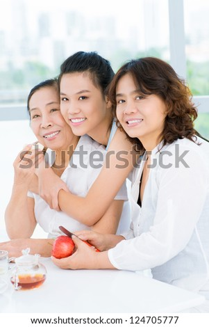 Three representatives of an asian family sitting at table and eating apples