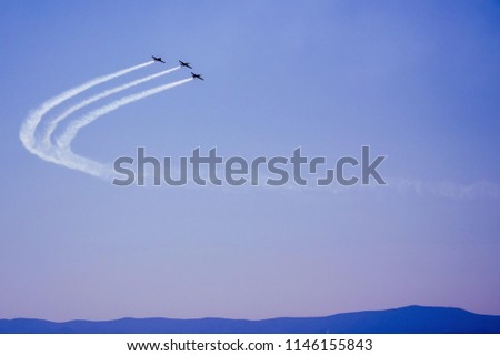 Three retro airplanes in the sky make a turn. On the blue background there is a white trace. Mastery of the pilot, teamwork, reaching new heights. Below is a line of hills.