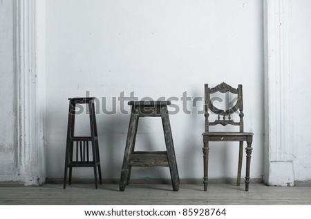 Three retro chair against a white wall.