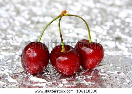 Three ripe berries of a sweet cherry on a foil