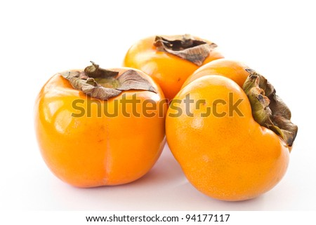 three ripe orange persimmons on a white background