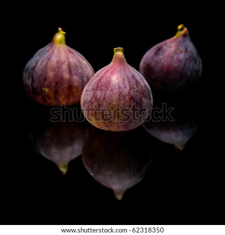 three ripe purple fig fruits isolated on black background, with reflection