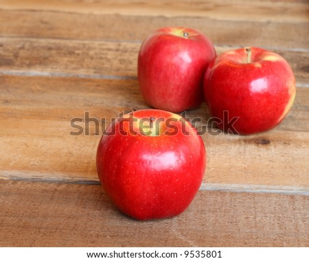three ripe red apples on a rustic wooden background with selective focus on the apple in front