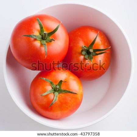Three ripe tomatoes in a white bowl - top view