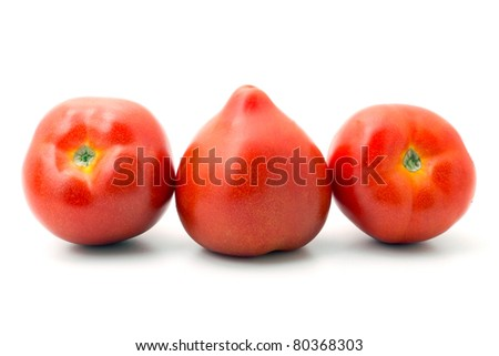 three ripe tomatoes lined up in a row on white