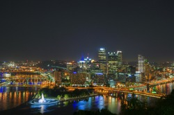 Three rivers meet in downtown Pittsburgh at night.
