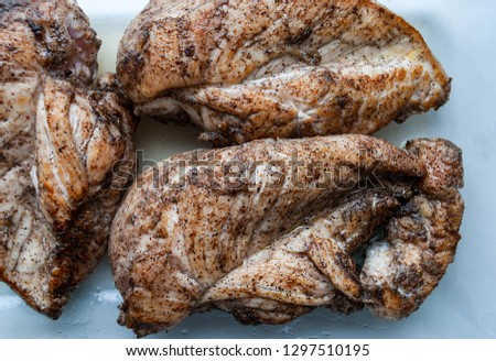 Three roasted chicken breasts with salt and black pepper in a glass container. Macro picture.