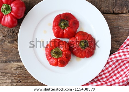 Three roasted, peeled and marinated red peppers on a white plate, next to a fresh pepper. Rustic take on old wooden table.