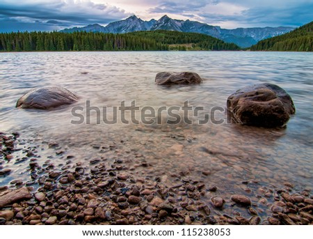 Three rocks in a ripply lake with forest and mountain peaks in the distance.