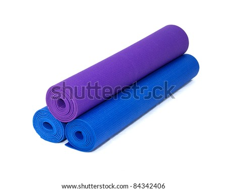 three rolled yoga exercise mats against white.