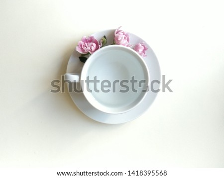 three rosebuds of violets of Saintpaulia lie over a white Cup on a saucer. in a mug of clear clean water. composition on a white background, flat layout, subject layout. #1418395568