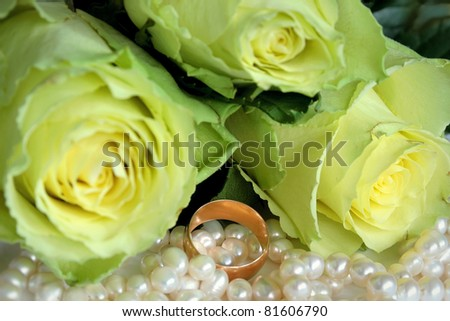 Three roses and a wedding ring lying on the pearl