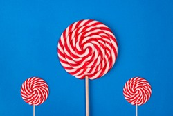 Three round lollipops of different sizes on a stick with red and white stripes on a blue background. Sweet round candy of red and white color. Sucking candy in the form of a spiral. christmas candy