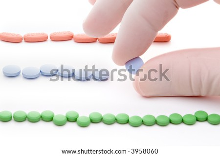 three rows of red green and blue pills and hand picking blue one