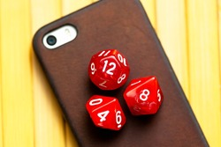 Three RPG polyhedral game dice, dice set laying on a modern smartphone. Role playing games, mobile phone apps for roleplay, board games. Chances, randomness and randomization in technology concept
