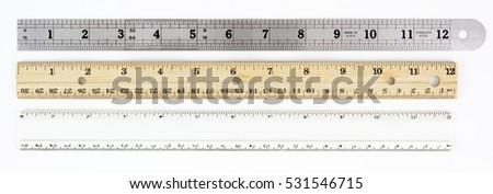 Three rulers: metal, wood, and plastic. Horizontal. Isolated.