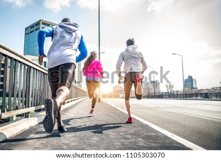 Three runners sprinting outdoors - Sportive people training in a urban area - healthy lifestyle and sport concepts