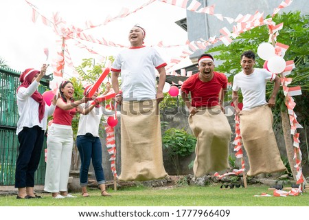 three sacks races tried to jump and run with supporting spectators on Indonesia's independence day celebrations on the field with balloons and small red and white decorations.