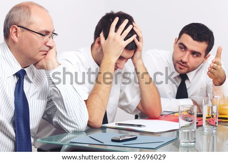 Three sad and depressed businessman sitting at table during meeting