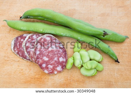 Three salami slices with fava beans on a wood chopping board