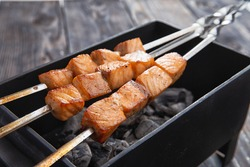 Three salmon skewers on a small grill. selective focus