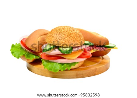 Three sandwich with sausage and vegetables on cutting board isolated on white background