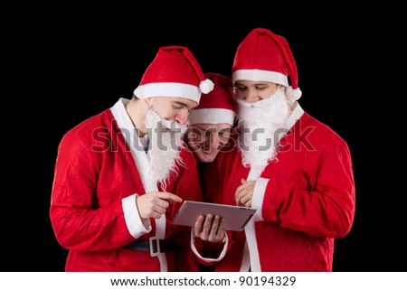 Three santa claus sending email on tablet PC