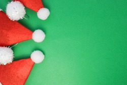 three Santa hats on the left on a green background. Background Layout greeting card for Christmas