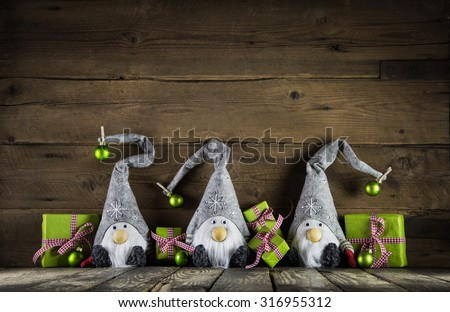 Three santa with red felt hats and apple green christmas presents on an old wooden background for decoration.