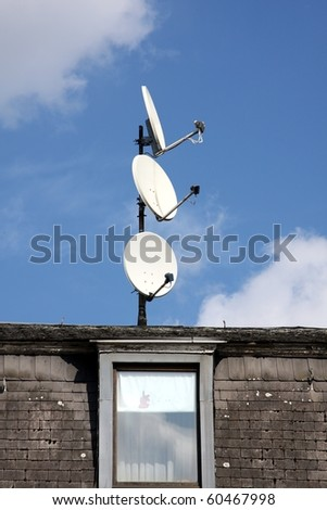 Three satellite dishes on a roof, pointing in different directions