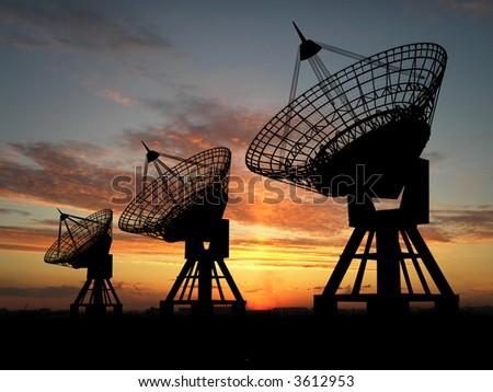 Three satellite dishes over sunset