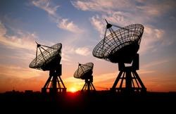 Three sattelite dishes at sunset