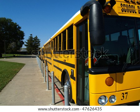 Three school buses parked along curb in parking lot