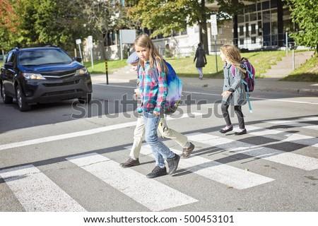 three school children crossing the street