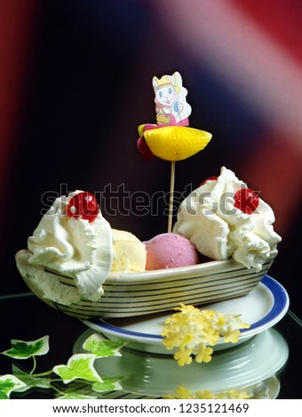 Three scoops of ice cream, strawberry, vanilla, chocolate and cream, in a ceramic boat, with a paper ornament.