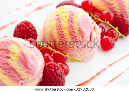 Three scoops of raspberry ice cream with fresh raspberries and red currants