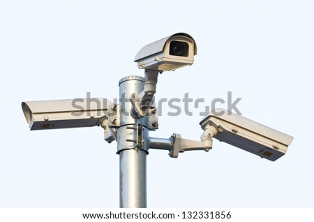 Three security cameras against the sky.