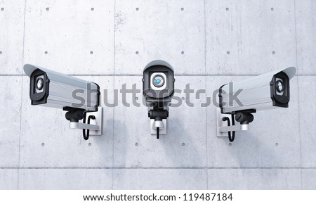 Three Security cameras frontal view on concrete wall