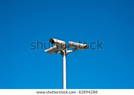 Three security cameras isolated on a blue sky