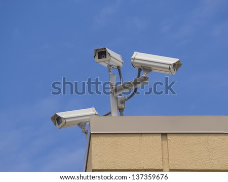 Three security cameras on a building against blue sky