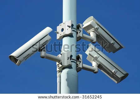 three security cameras on blue background