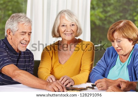 Three senior citizens playing a domino game in a nursing home
