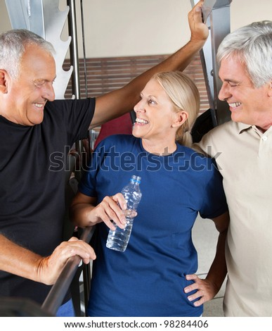 Three senior people talking in gym while having a break - stock photo